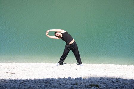 Young man stretching on beach Stock Photo - 10930221