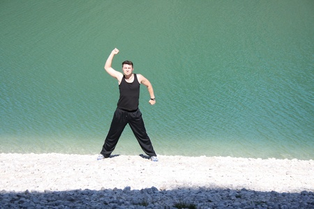 Young man stretching on beach Stock Photo - 10930248