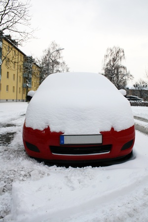 red car in city street in winter   photo