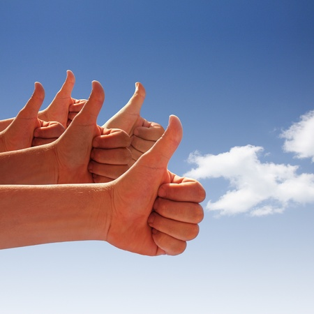 mens hands make thumbs up on blue sky photo