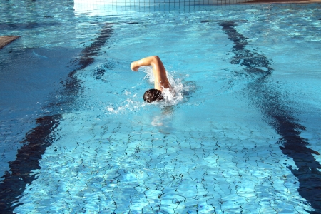 man swims in swimming pool photo
