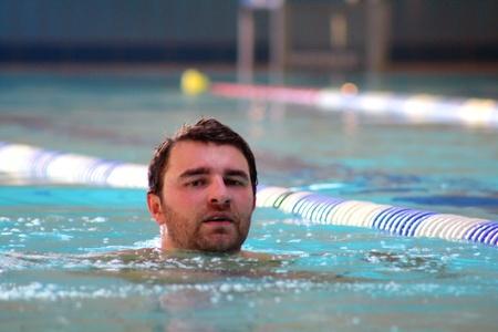 man swims in swimming pool photo