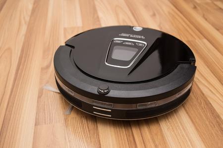 carpet clean: Robotic vacuum cleaner on wood parquet floor, Smart vacuum, new automate technology housework.