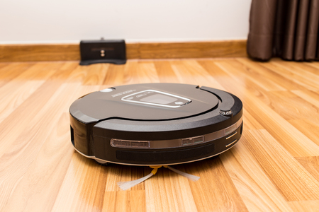 Robotic vacuum cleaner on wood parquet floor, Smart vacuum, new automate technology housework.