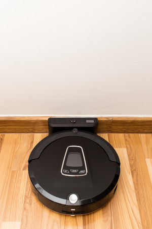 automate: Robotic vacuum cleaner on wood parquet floor, Smart vacuum, new automate technology housework - Auto charging at dock station.