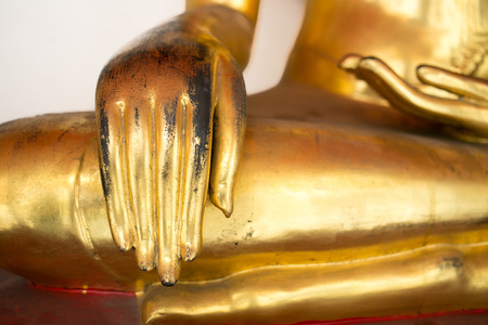 Right Hand of Old Gold Buddha statue sit cross legged.