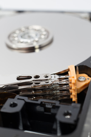disassemble: Inside Hard Disk Drive HDD-Computer Hardware Components Focus on Actuator Arm.
