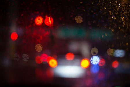 foreground focus: rain drop with street colorful traffic lights at night blur bokeh abstract background vintage color tone, Cool chill wet raining season concept