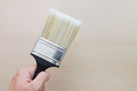 paintbrush spray: male hand hold paint brush with wooden background