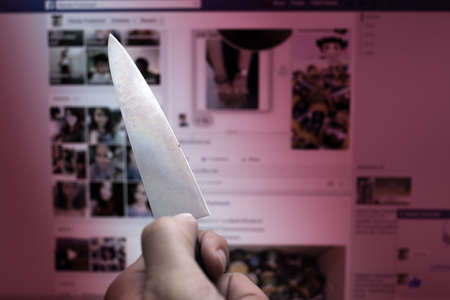 assassinate: knife with mouse in dark tone,computer online or social network killer murder concept