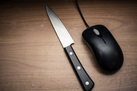 despatch: knife with mouse in dark tone,computer online or social network killer murder concept