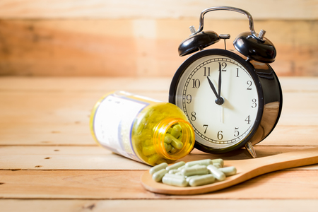 sleeping pills: medical capsule with clock on wood table, take a pill on time concept.