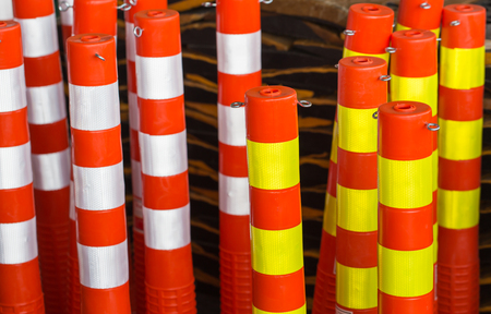 roadwork: close up Traffic pole with white and yellow light reflector color stripe. Stock Photo
