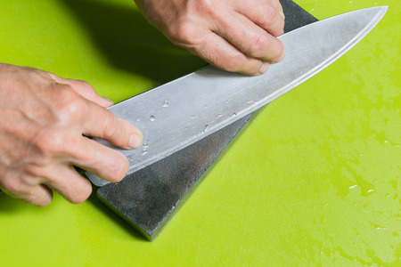 hand sharpening chopper with grindstone in the kitchen, kitchen knife.