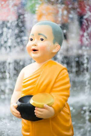 Close up Cute Kid Thai Monk Statues of Buddhist doing Morning Alms Round.