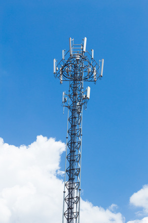 Cell site, Telecommunications radio tower or mobile phone base station with cloud and blue sky background