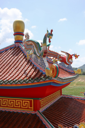 chinese phoenix: Chinese phoenix statue on roof with cloud and blue sky. Stock Photo