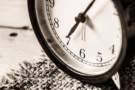 seven o'clock: Retro vintage clock on sack closeup at 7 oclock