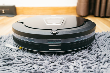 Robot vacuum cleaner on laminate wood and carpet floor, Smart robotic automate wireless cleaning technology machine in living room. Stockfoto
