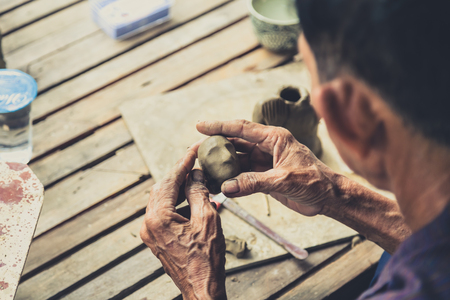 wallop: Professional Thai sculpture handcraft artist molding clay as head of buddha by hand.