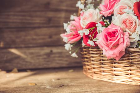 vintage flower rose in the basket on old wood background.