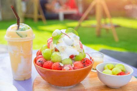 Bingsu dessert, Summer season sweeten Asian lifestyle menu eat cooling sweet iced with delight delicious fruit topping and blended Peach smoothie drink, Korean style Shaved Ice dessert.
