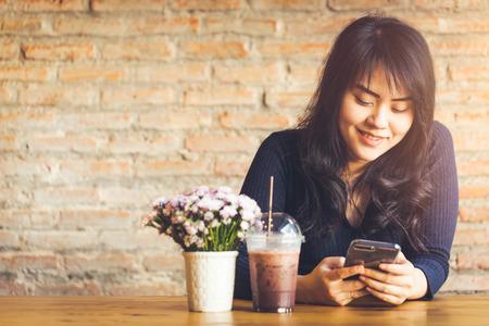 Het gelukkige ogenblik met smartphone, Aziatische vrouwentiener die haar het scherm van de mobiele telefoonlezing bekijken en glimlacht bij de koffiewinkel of toon van de koffie de uitstekende kleur.