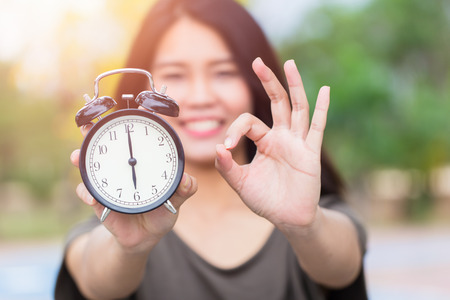 Times is OK or Right time with right job concept, Asian women hand show clock times with hand show good alright sign.
