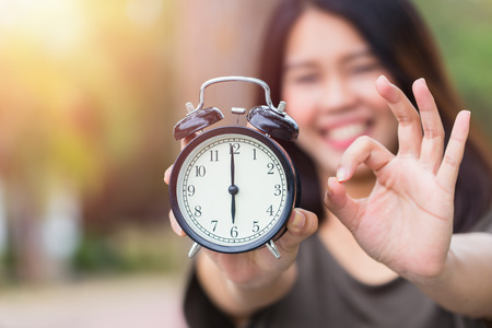 alright: Times is OK or Right time with right job concept, Asian women hand show clock times with hand show good alright sign.