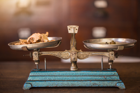 vintage herbal shop, dried galangal on old balance scale in herb store.
