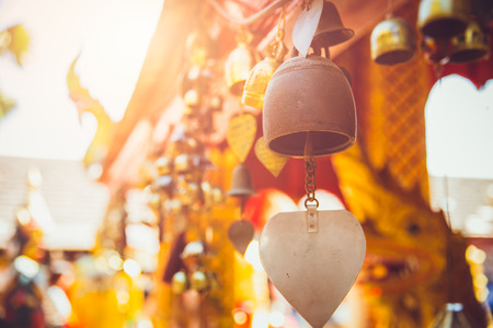 Old Brass Bell in Thailand temple. Buddha worship copper golden small Buddhist bell hanging at chapel. Stock Photo