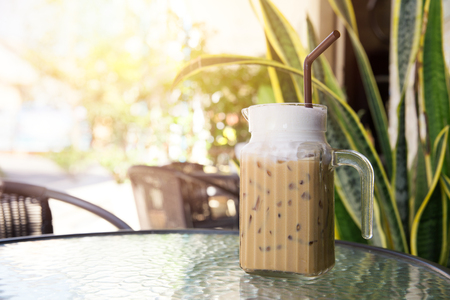 Iced Coffee Latte with Ice outdoor coffee shop with green garden.