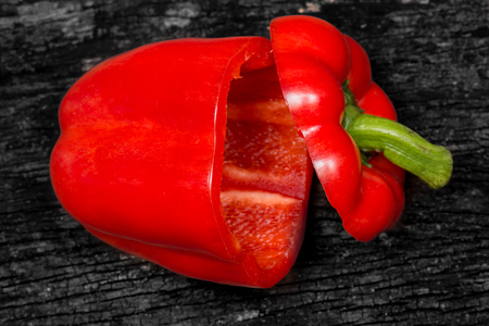 cutted: closeup Red Bell pepper cut on dark wood background.