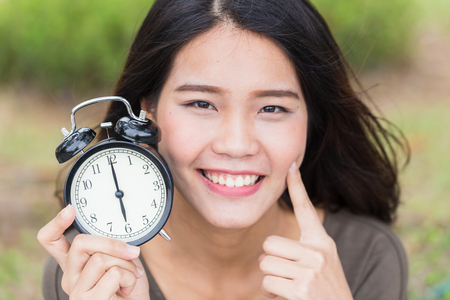 reverse: baby face, timeless cute asian women girl with young skin look with clock time. Stock Photo