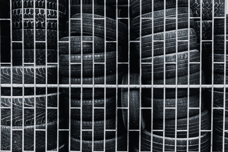 dirty car: old used tire keeping in the cage for recycle. Stock Photo