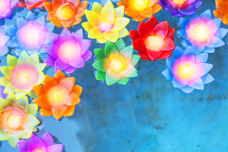 colorful flower light candle float in the water pond. Stock Photo