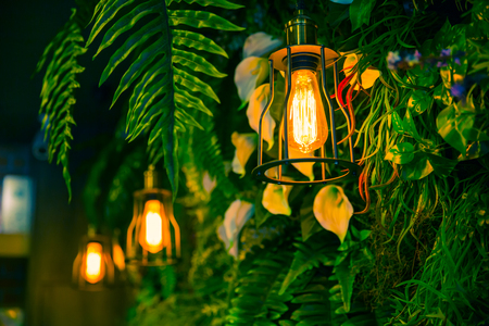 outdoor lighting: Jungle lamp in the forest green plant background interior cafe decoration.