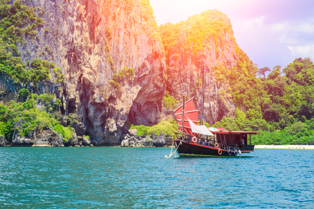 Chinese barque boat at Thailand summer travel sea, Thai old wood boat at sea beach Krabi Phi Phi Island Phuket park on white sand blue sky emerald green ocean water. Stock Photo