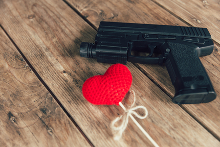 love hurts: pistol gun and love red heart on wood background