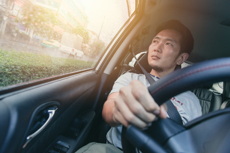 Asian man male drive a car and looking at the windows.