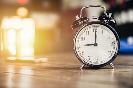 numero nueve: Reloj retro de las 9 en punto en la mesa de madera con fondo de luz del sol Foto de archivo