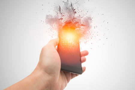 smartphone explosion, blow up cellphone battery or explosive mobile phone or explode burst fire burn out smart device with dispersion effect. Standard-Bild