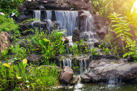 Artificial small Water fall in the park garden home green space decoration. Stock Photo
