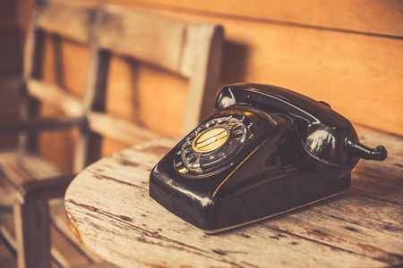granddad: old telephone black color on wood table. classic retro vintage style rotary dial calling telephone type number.