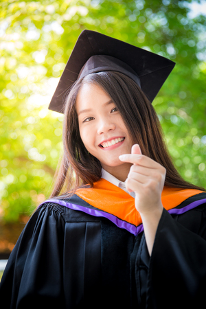 Asian cute women portrait graduation with green nature background, Thailand university.