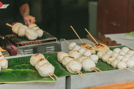 meatloaf: Big Meat Ball from pork product with Bamboo stick Grill sale at street food in Thailand. Stock Photo