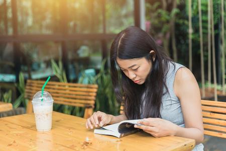 El día de fiesta asiático de las mujeres paga la atención en el libro de lectura del autoaprendizaje de la educación en jardín con cafetería.