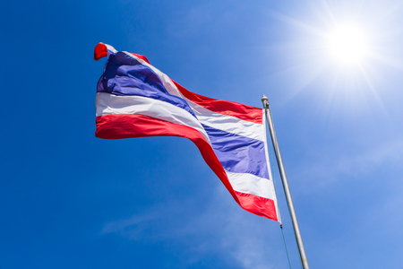 Thai flag of Thailand with blue summer sky sunny day background.