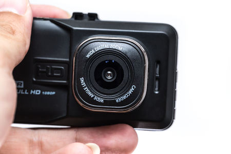 closeup digital camera action cam or dash cam show font lens in hand on white background