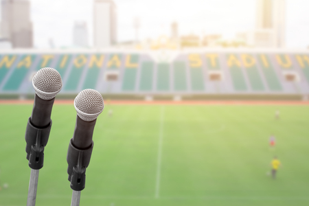 Microphone for commentator with sport football field stadium background with space for text